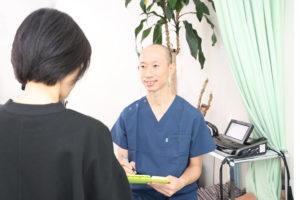 うの整骨院院長宇野彰男がお客様にカウンセリングをしている写真
