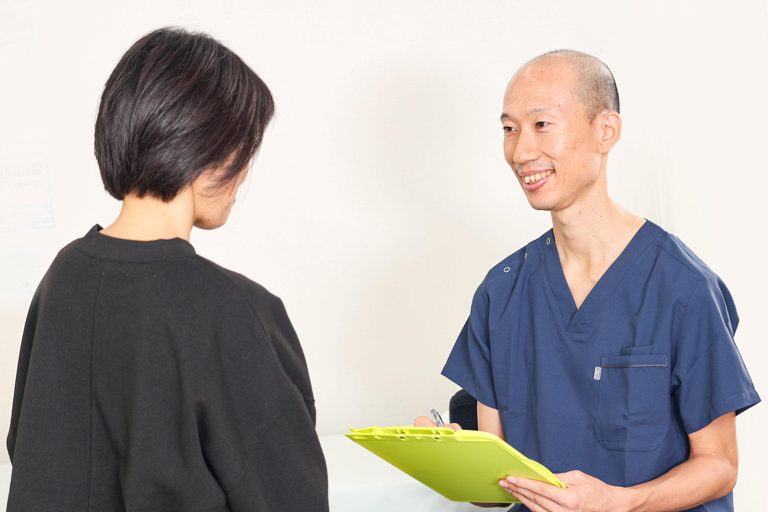 問診で患者様にどんな痛みや不調があるのか詳細に聞いている院長