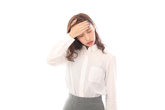 頭痛がある30代女性が頭をかかえている