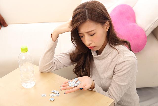 頭痛に悩む20代女性が頭痛薬を飲むか迷っている