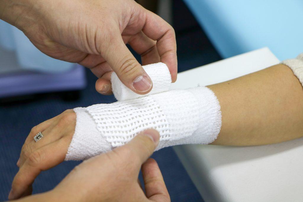 整形外科勤務時に骨折の患者様に包帯処置を丁寧にしている院長