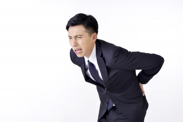 慢性的な腰痛になり、腰の痛みで腰をかがっている40代男性
