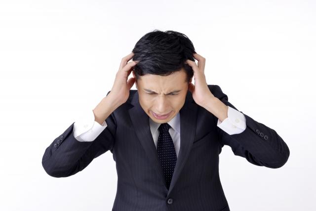 頭痛で悩む40代男性が頭をかかえて痛みをこらえている