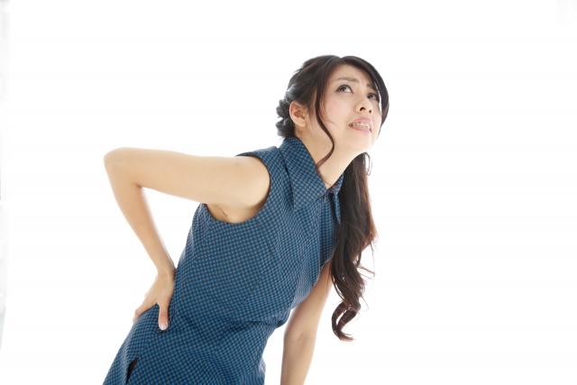 腰痛症で腰の痛みが酷く腰を抑えている40代女性