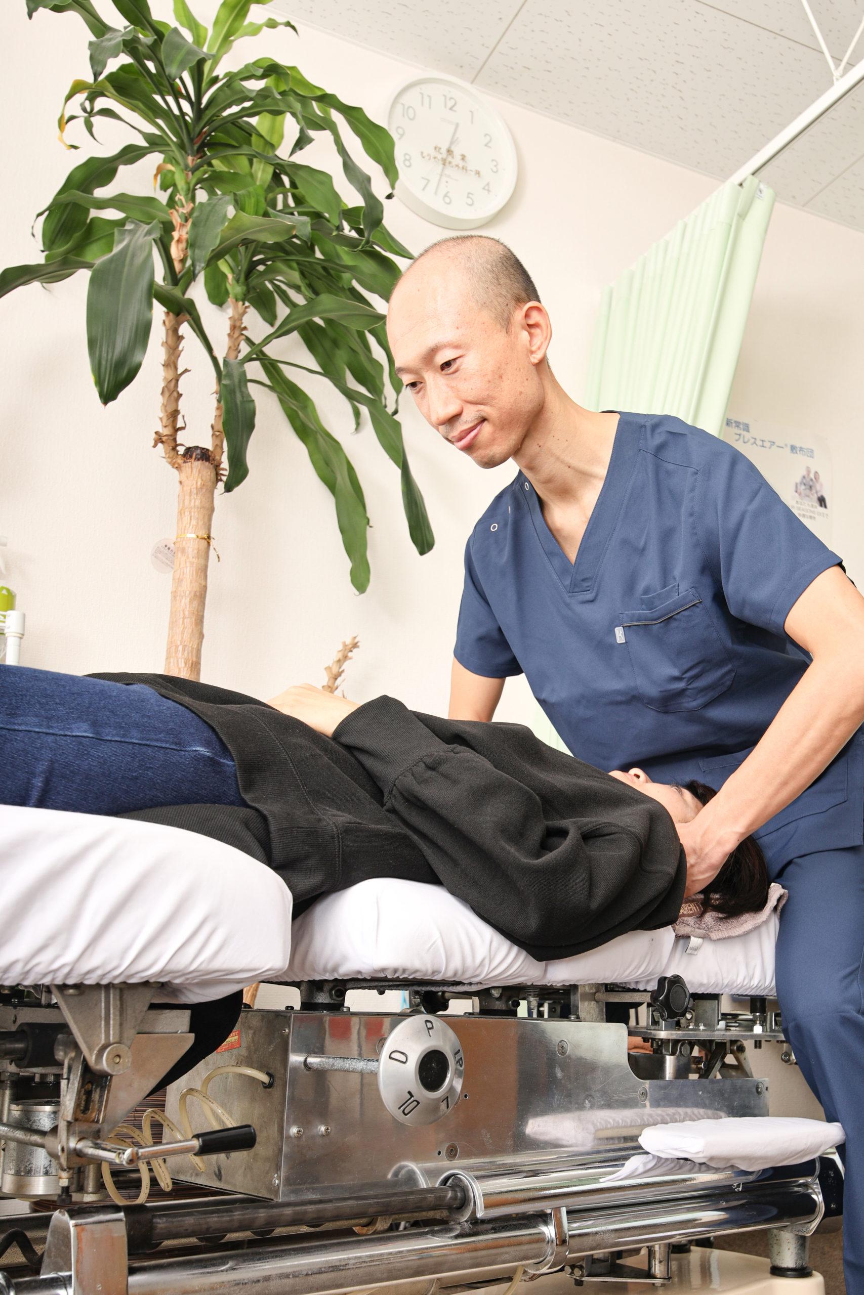 カイロプラクティック専用ベットであるトムソンベットで40代女性の首の骨を調整する院長