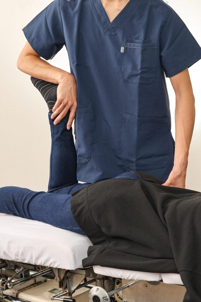 骨盤の可動性検査と筋力検査をしている院長