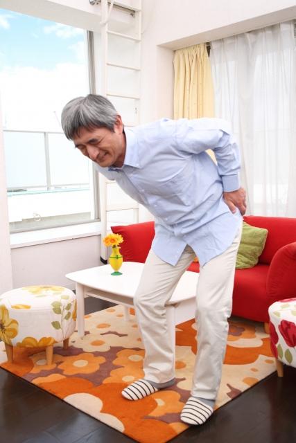 変形性脊椎(腰椎)症の腰痛で腰を痛めて腰を押さえている50代男性