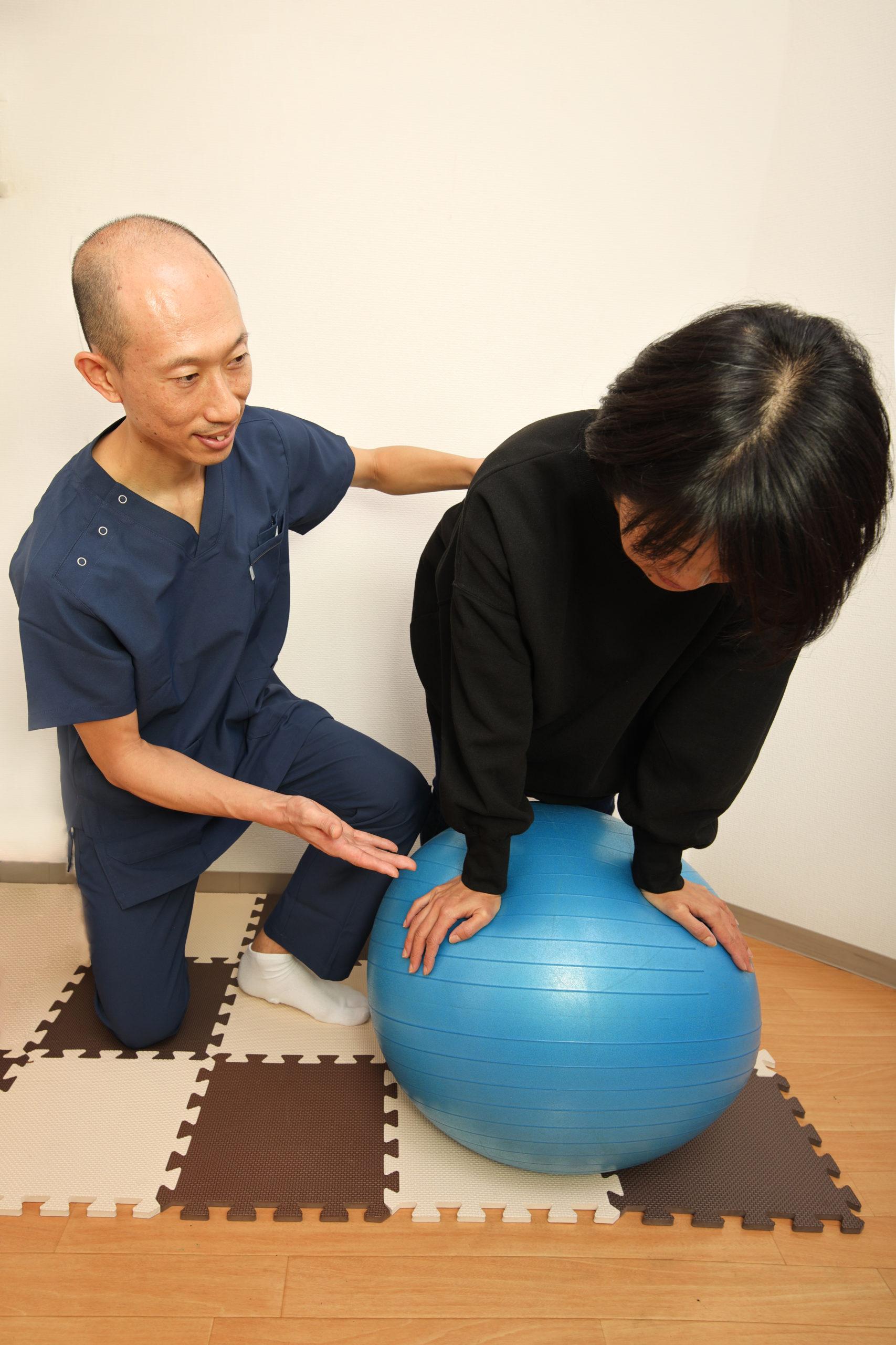 40代女性にバランスボールエクセサイズで姿勢矯正・姿勢改善を促すエクセサイズをアドバイスしている院長