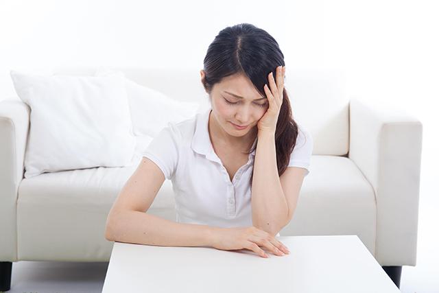 頭痛のある40代女性が座ってうつむいている