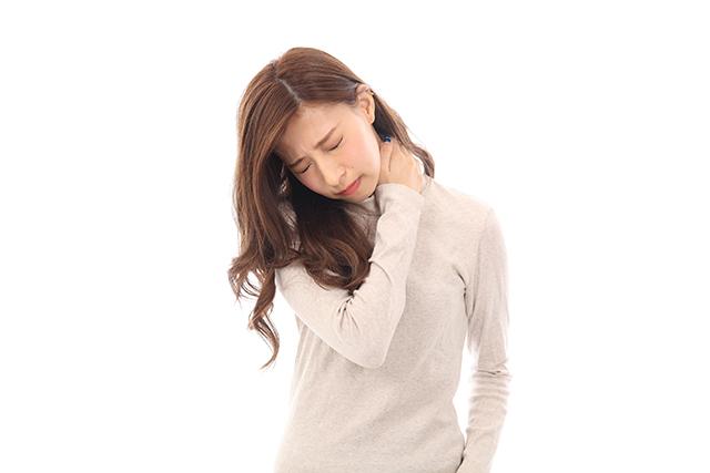 肩こりに悩む30代女性が辛くて肩を押さえている