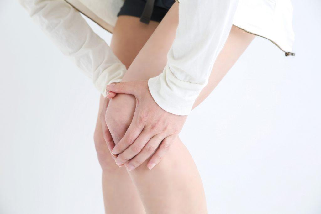 左膝が痛くて、痛みを手で押さえる30代女性