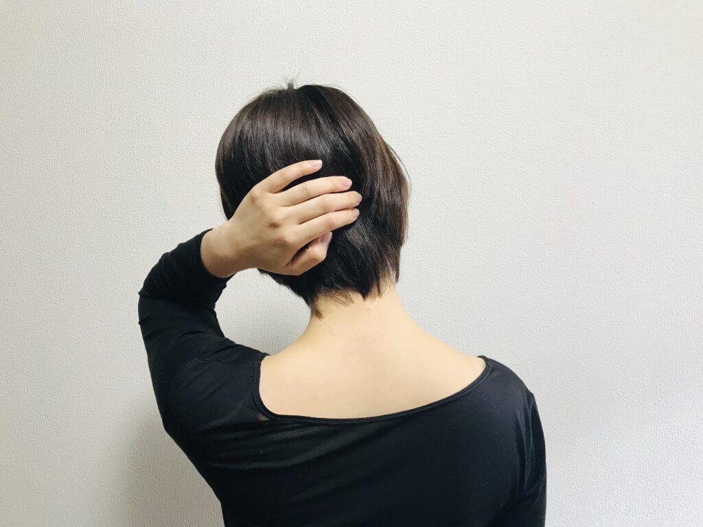 交通事故でむちうち症になり首がほとんど回らなくなった40代女性の首の動きを検査している院長