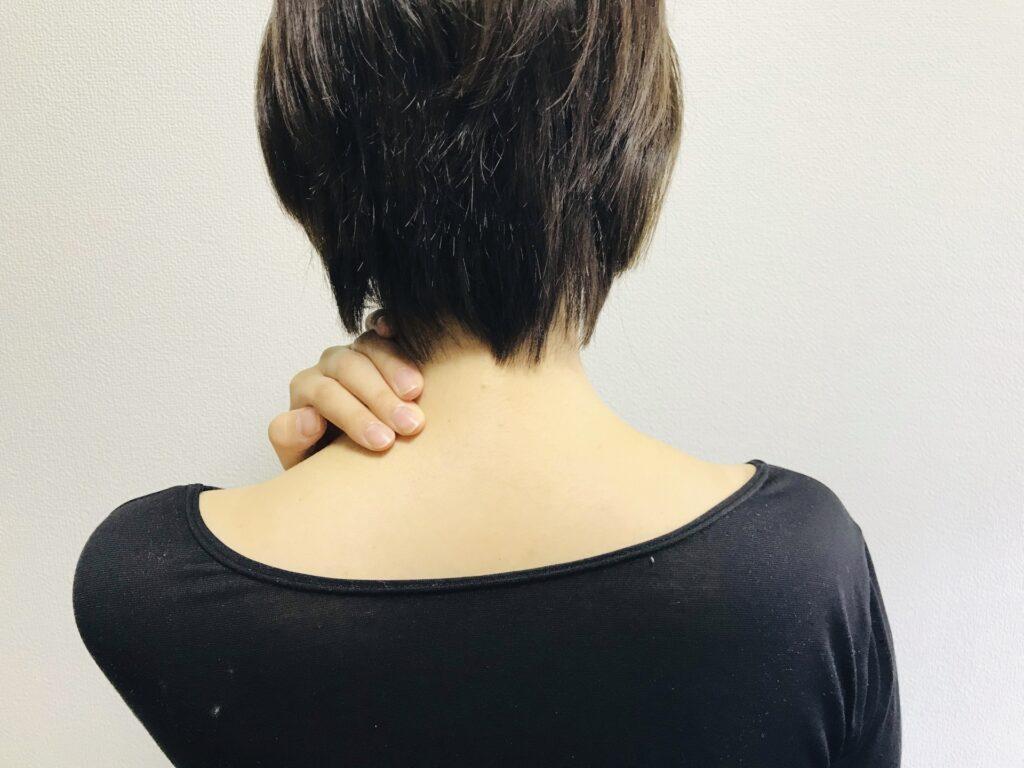 交通事故でむちうち症になり首がほとんど回らなくなった40代女性が痛む首を抑えている
