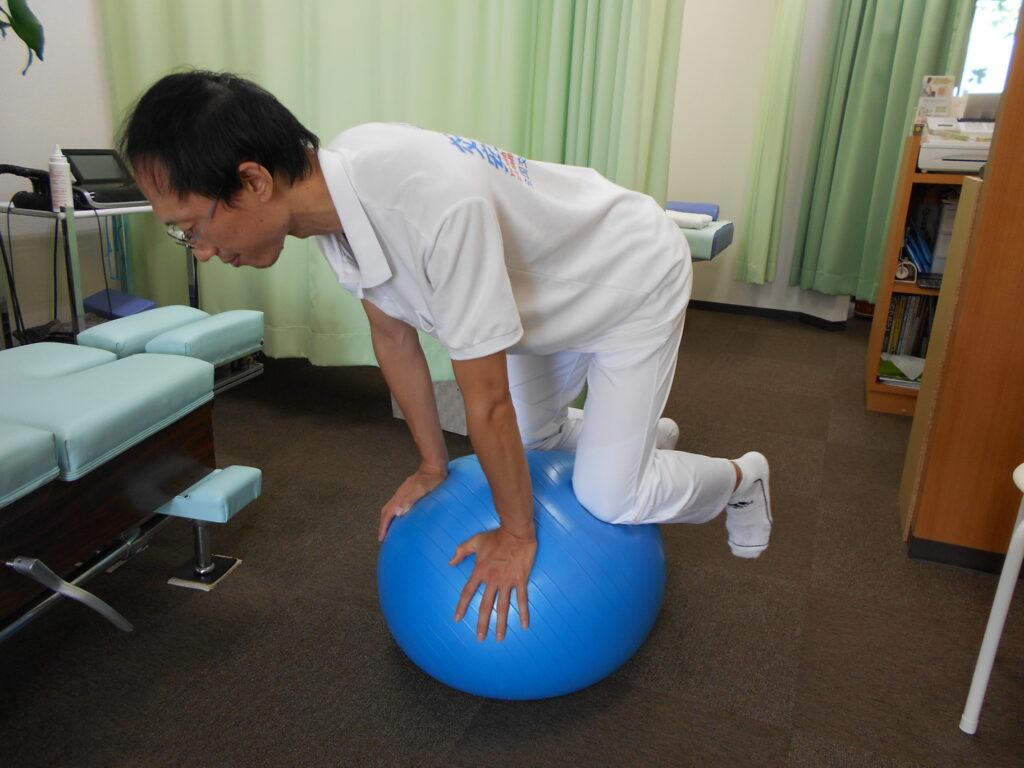 腰痛に役立つインナーマッスルを鍛えるバランスボールエクセサイズを患者さんにレクチャーする院長